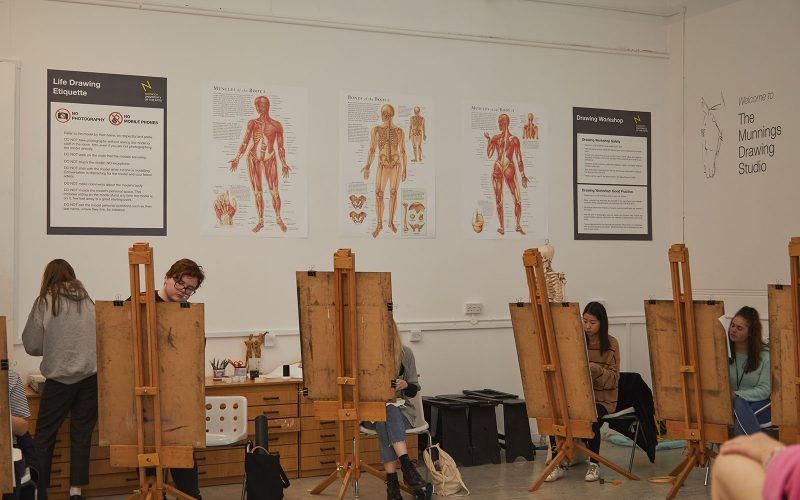 Students sit by easels in Munnings Drawing Studio at Norwich University of the Arts