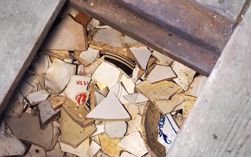 Photo of bare floorboards showing broken ceramic pieces underneath