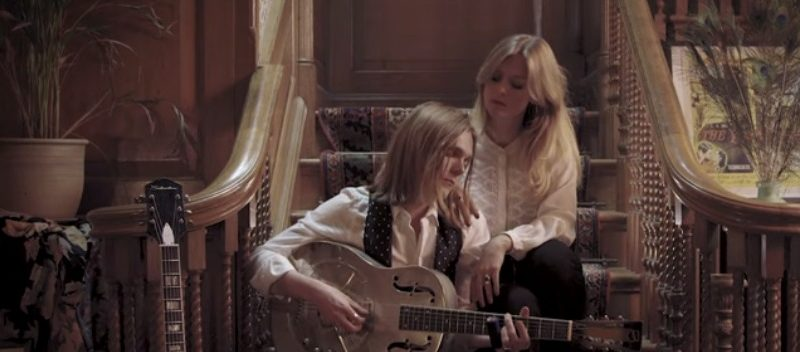 Screenshot from Ida Mae's video of man sat with guitar with female singer on stairs directed by TP Hyland, BA Film and Moving Image Production graduate from Norwich University of the Arts