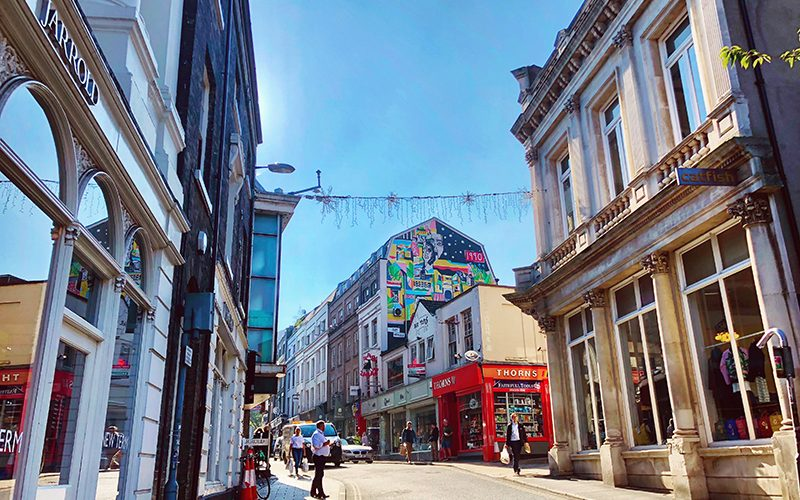 Photo of a sunny day in Norwich looking up Exchange Street to Thorns and a large wall mural