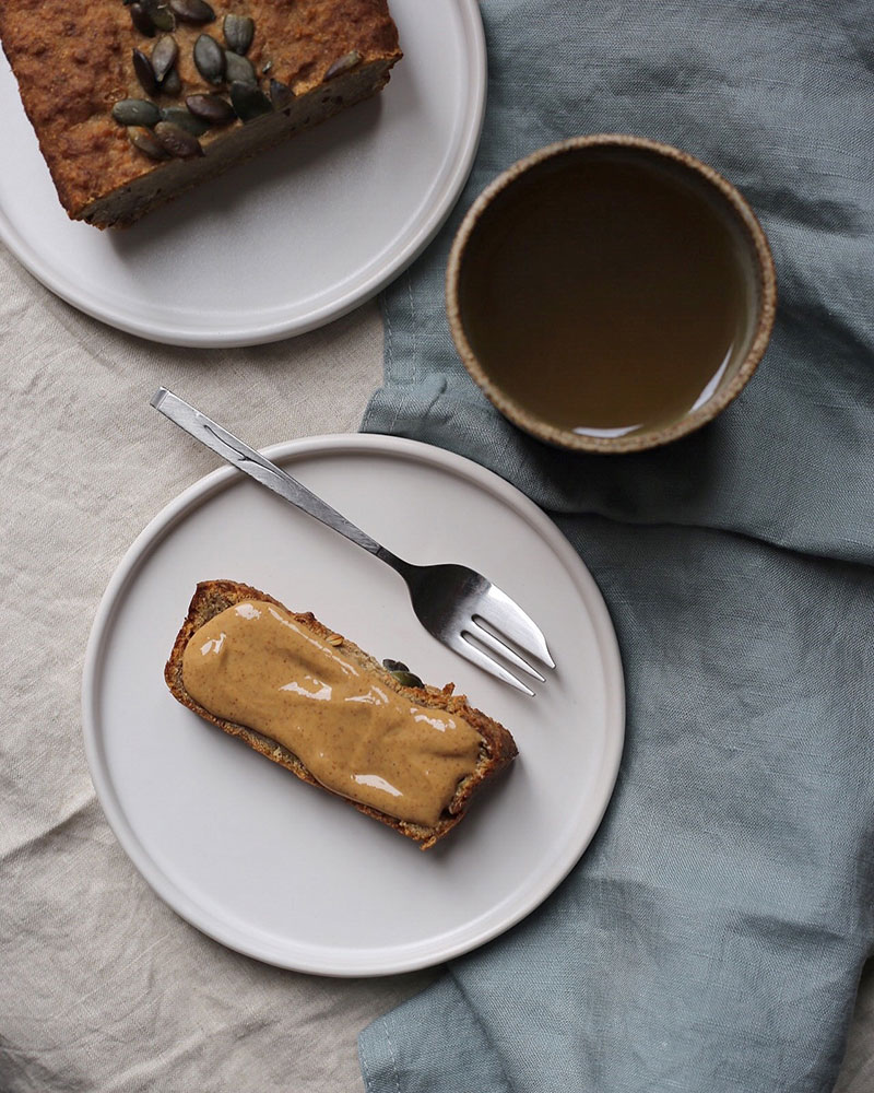 Banana bread on a plate with cup of tea and napkin by Norridge Porridge