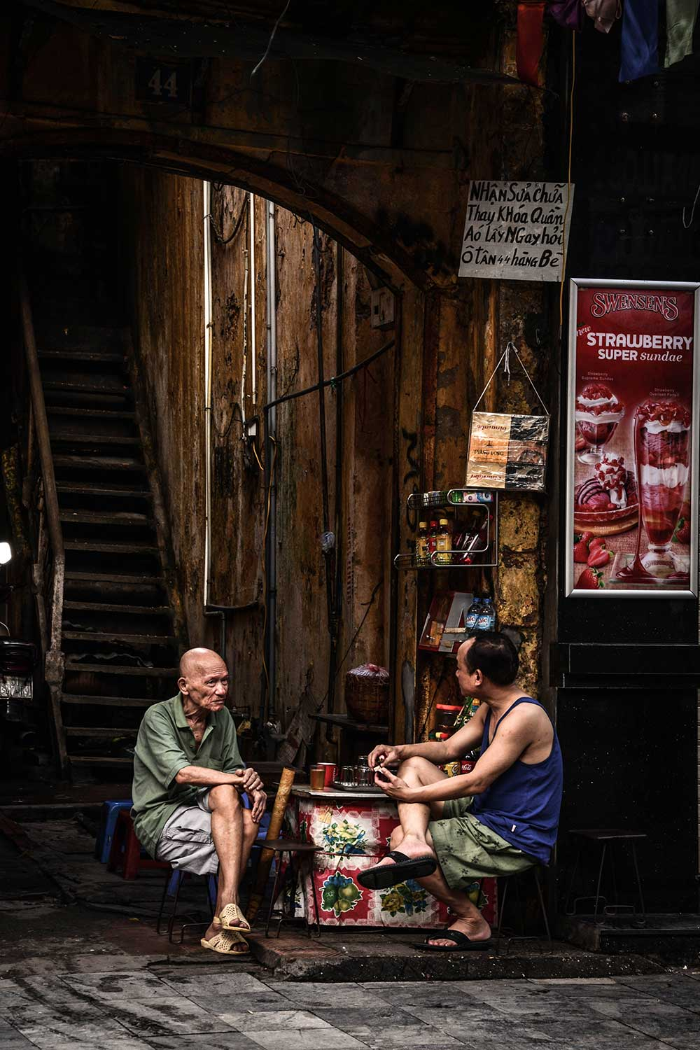 Two people sitting in a Thai street at a table by Chalisa Chanchuvanichkul, Norwich University of the Arts Graphic Design student