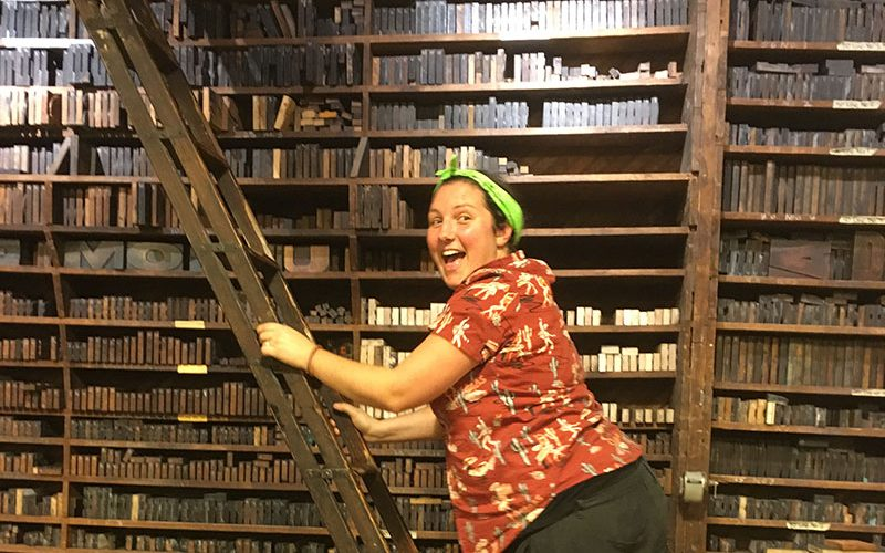 Jo Stafford, Print Technician at Norwich University of the Arts climbs a ladder by a bookcase in a print studio in the US