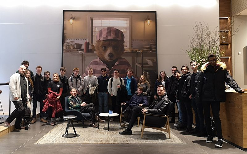 Group photo of VFX students and staff inside a large room in front of a large image of Paddington bear