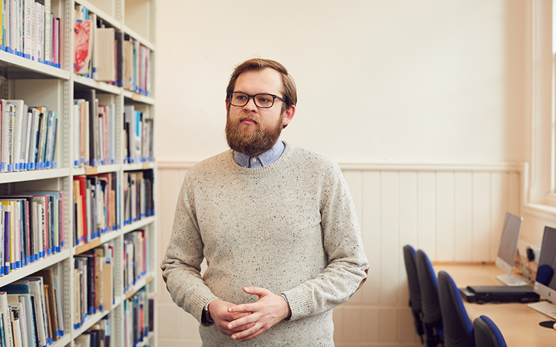 Man in light grey jumper stood next to library shelves
