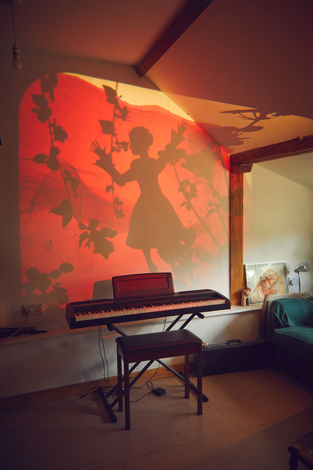 Professor Suzie Hanna's studio showing an animation of a girl with trees on a wall by a piano and stool