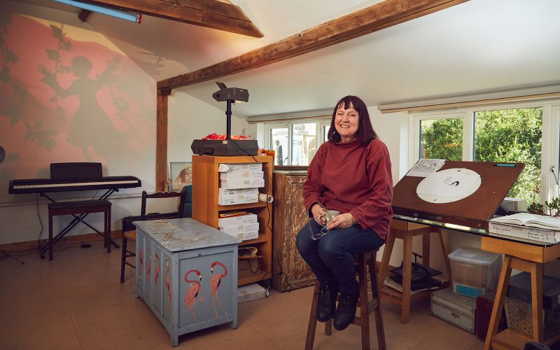 Professor Suzie Hanna, Animation Lecturer at Norwich University of the Arts sits in her home-made studio on a stool.