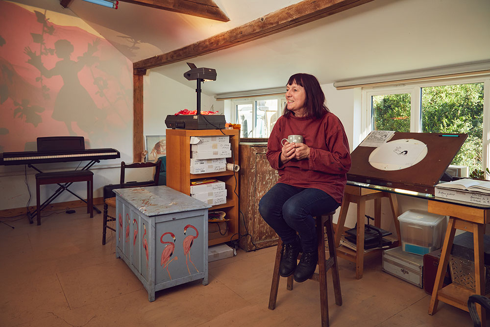Suzie Hanna professor of Animation sitting on a stool with a cup of tea in her home-made animation studio