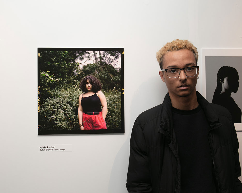 Isiah Jordan of Suffolk One Sixth Form college standing next to his square image of a girl by a bush