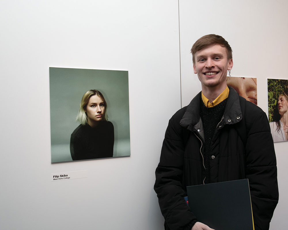Filip Skiba from West Herts College stood next to his image of a girl staring in the Beyond the Frame competition