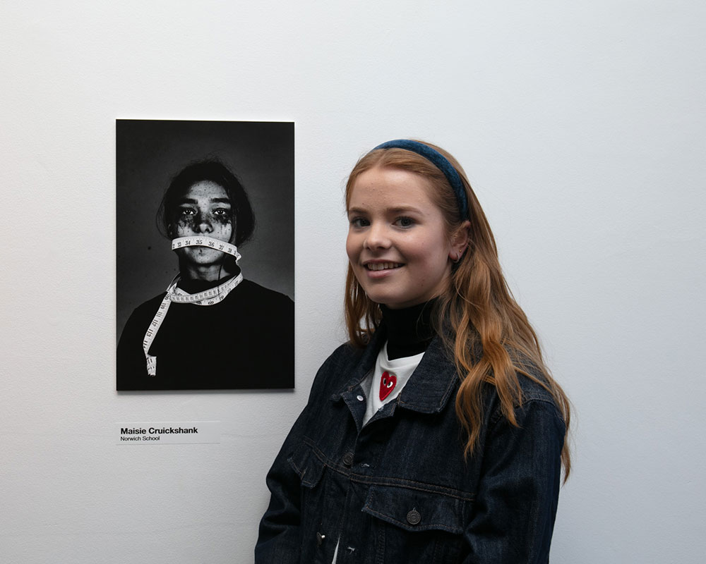 Maisie Cruickshank from Norwich School standing next to her image of a girl with a tape measure around her mouth