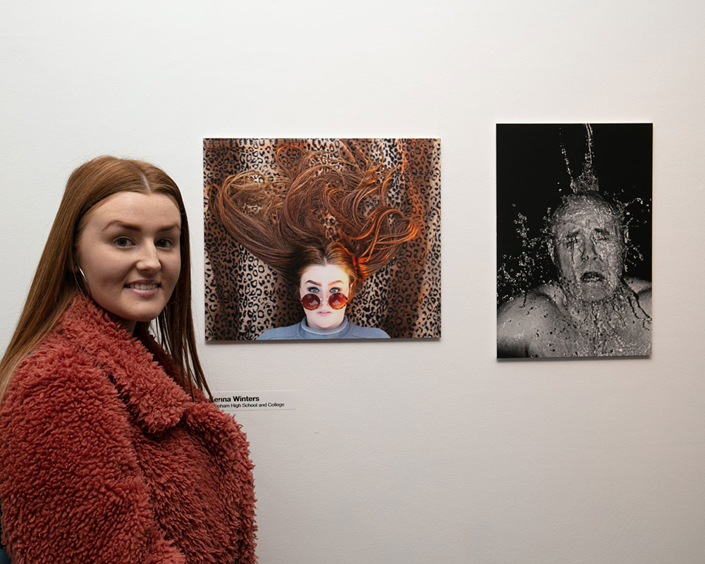 Kenna Waters standing next to her image of a girl with her hair in hearts over a leopard print cloth