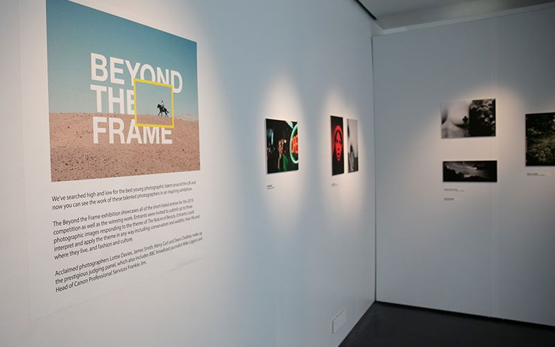 The interior of the Beyond the Frame exhibition at Norwich University of the Arts showing images attached to the wall