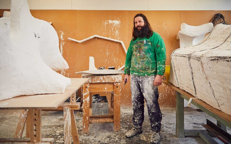 Fine Art Lecturer, Desmond Brett stands in his Fine Art studio surrounded by his sculptures