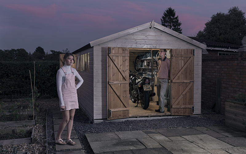 Dark coloured photo showing a man stood in the doorway of a garden shed and a young woman dressed in pale pink just next to the shed
