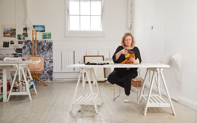A woman with blonde hair sat at a white trestle table holding a shoe prototype