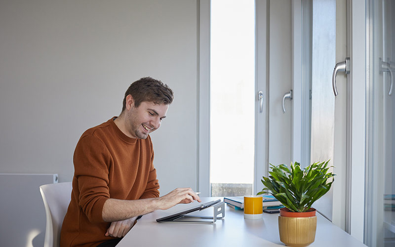 A man with light brown hair sits at a white table with a plant on it