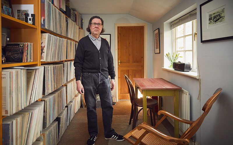 Rob Hillier, graphics Lecturer at Norwich University of the Arts standing next to vinyl records in his studio/house
