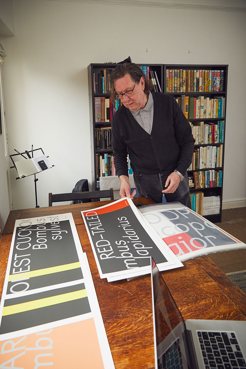Rob Hillier standing by his typographic work in his home-made Norwich studio