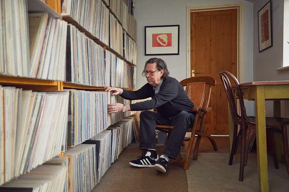 Rob Hillier, graphics Lecturer at Norwich University of the Arts sits looking through his records in his studio