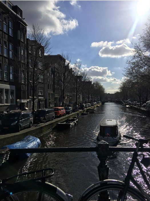 View of Amsterdam down a canal with sun shining and blue sky