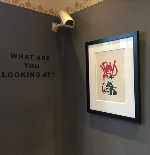 Art by Banksy hung in a gallery in Amsterdam with the words 'What are you looking at' next to it