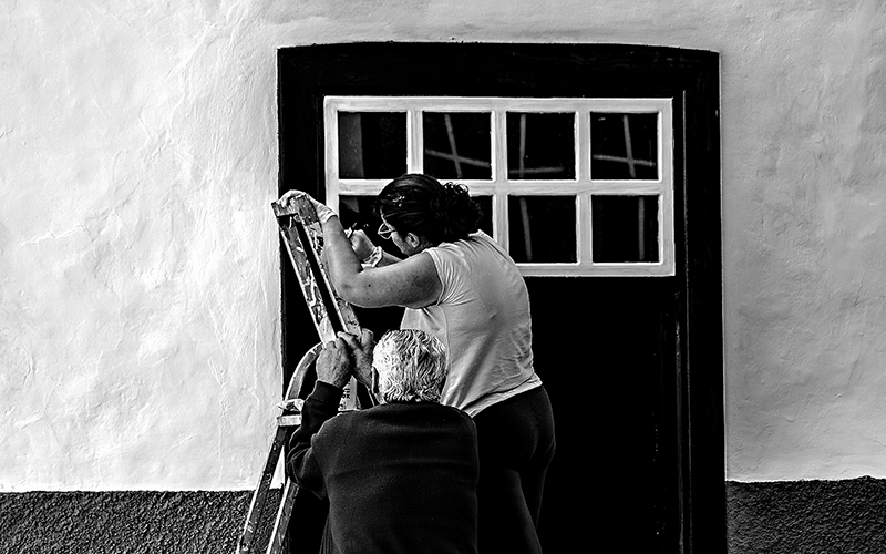 Monochrome image of a woman on a ladder
