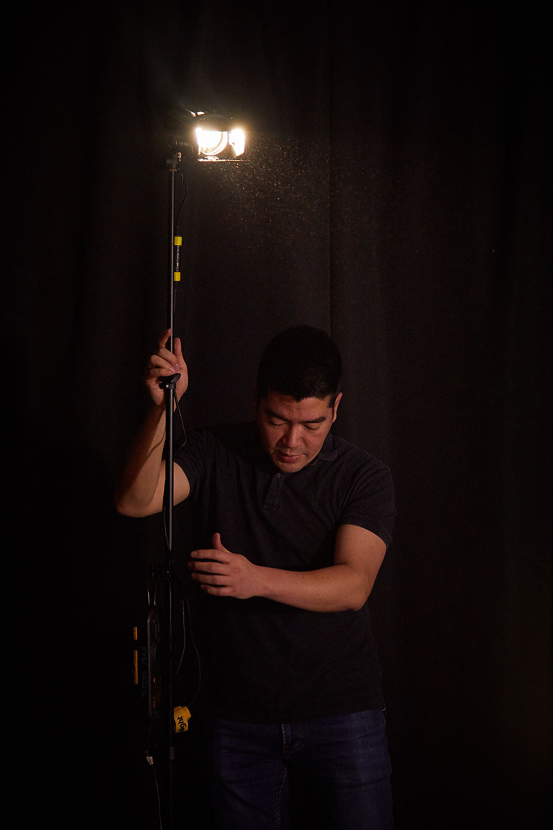 Roter Su, film Lecturer setting up a light on set