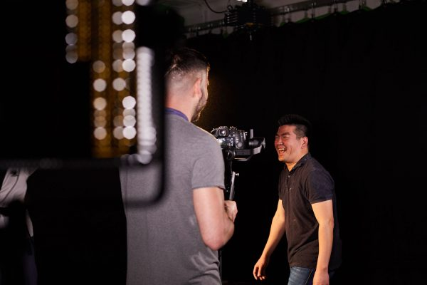 Roter Su - Roter Su, Lecturer in Film at Norwich University of the Arts stands by a light on a film set laughing whilst talking to camera operator