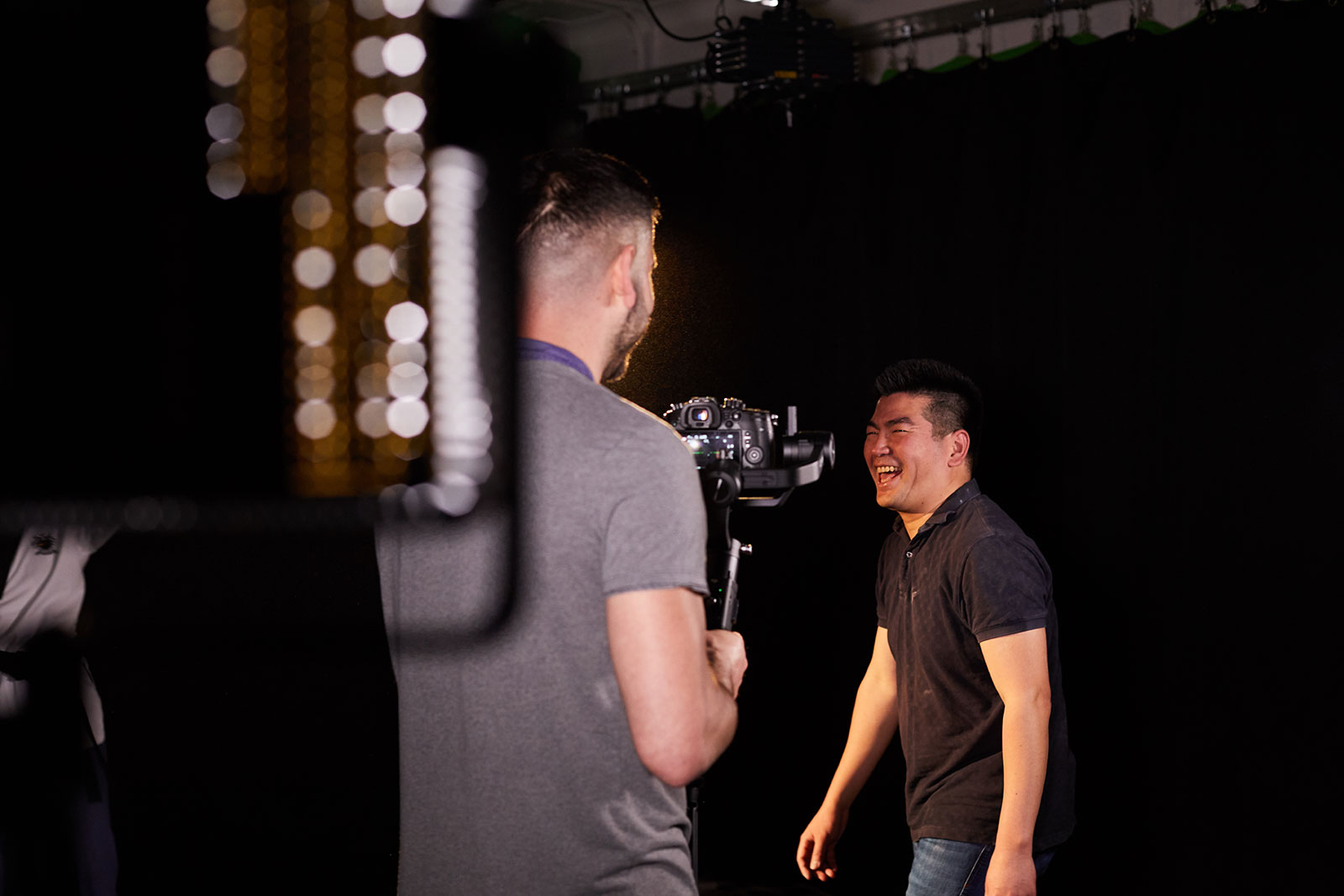 Roter Su, Lecturer in Film at Norwich University of the Arts stands by a light on a film set laughing whilst talking to camera operator