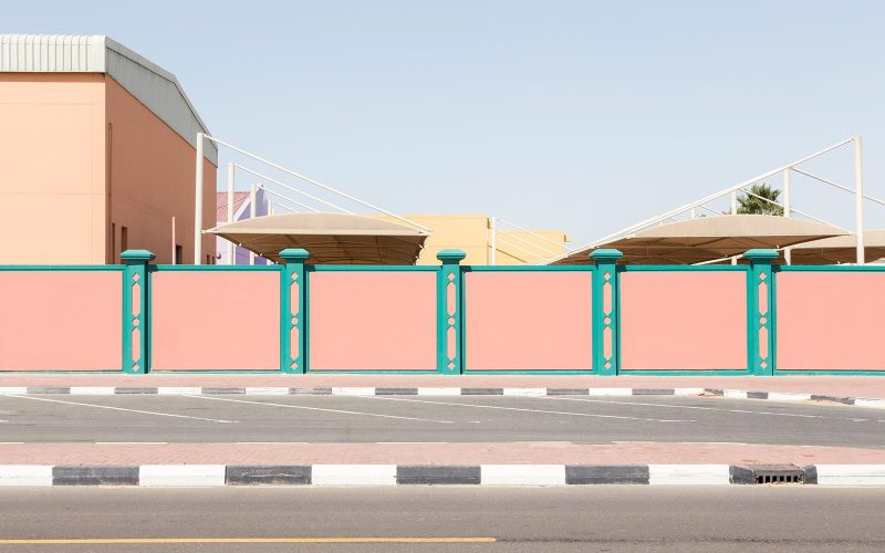 Photo of a wall by BA Photography student Lara Chandler. The wall is pink with green stripes and located next to a road in Dubai.