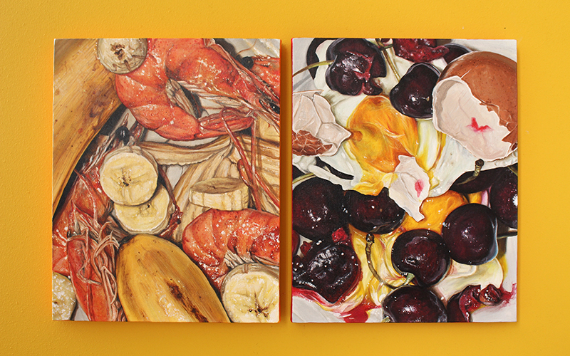 Two brightly coloured paintings depicting cherries and sliced banana on a bright yellow background