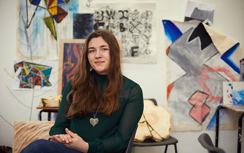 female student sat down smiling into the camera, with various art in the background