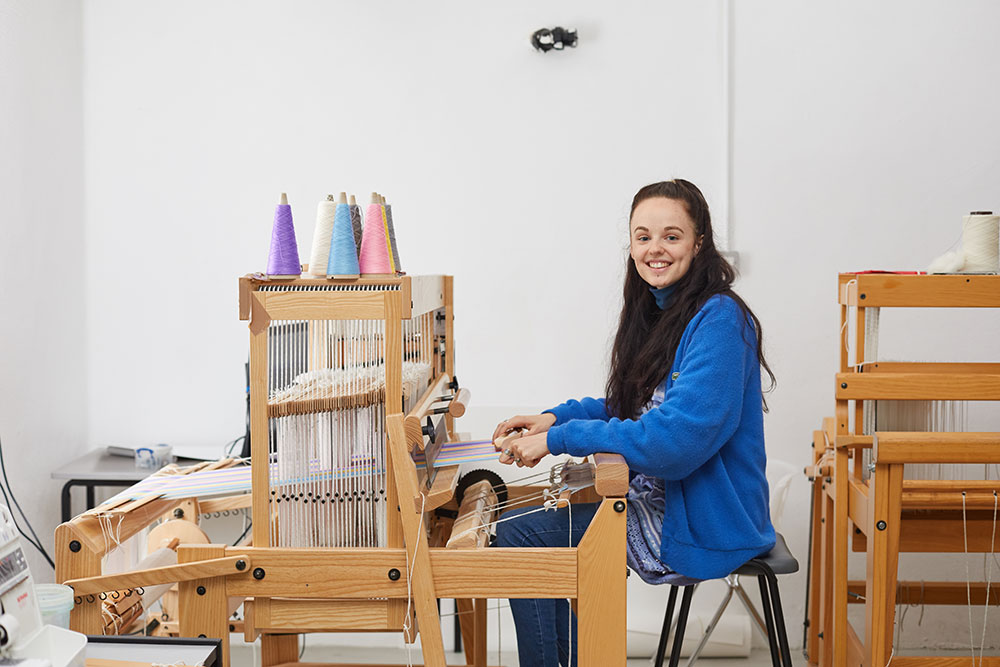 Rebecca Hiscock sitting at loom