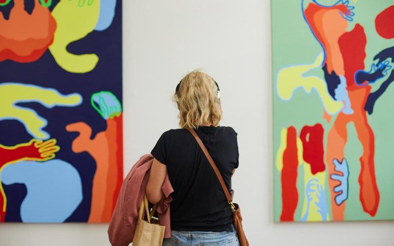A visitor wears headphones at the Norwich University of the Arts Degree Shows and looks at brightly coloured art