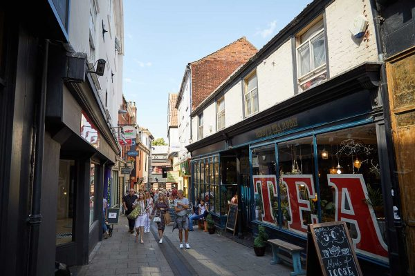 Norwich Lanes - People walking down Lower Goat Lane and Biddys tea room with the words 'tea' in the windows at the Norwich Lanes Fair