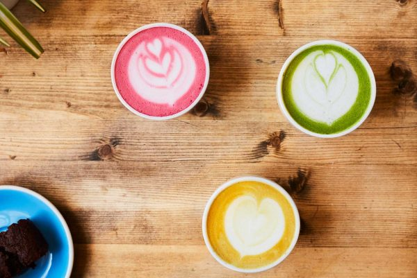 Jordan Hudson - 1 pink coffee, 1 yellow coffee and 1 green coffee on a table in Ancestors Coffee, Norwich