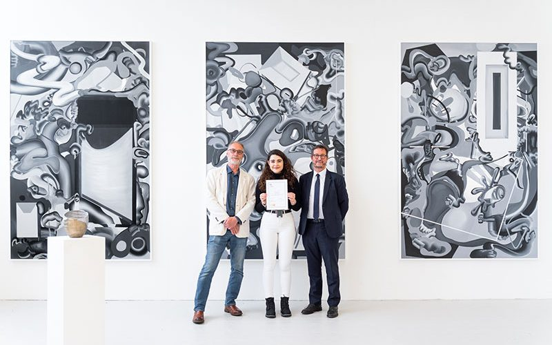 Brian Davey, Aurelia Coster and Vice Chancellor John Last OBE at the presentation of Aurelia's prize standing in front of her Fine Art work at Norwich University of the Arts