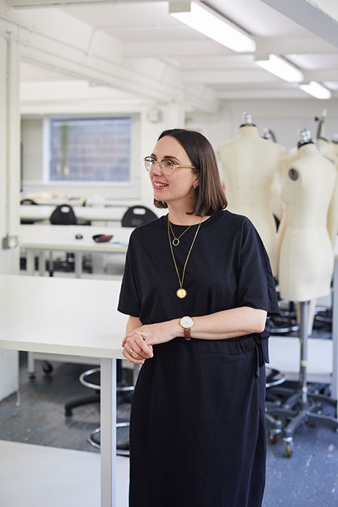 BA Fashion Lecturer Nina Dobson standing in front of two mannequins in the Norwich University of the Arts Fashion studio