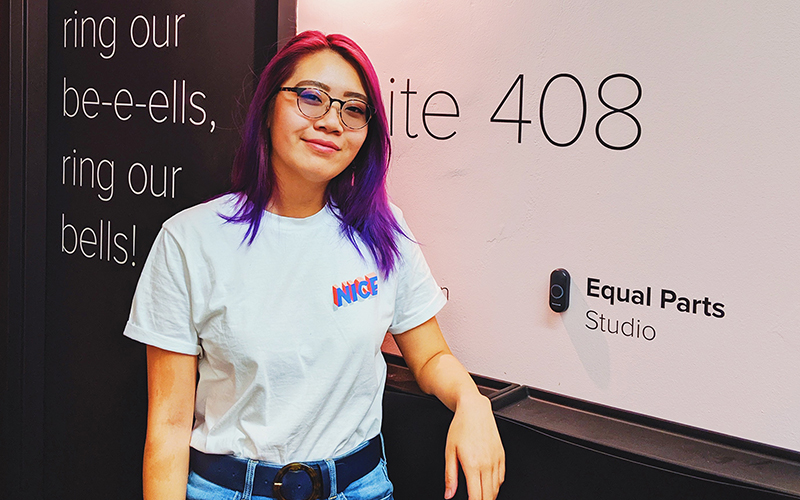 Young woman in a white tshirt and pink and purple hair leaning against a wall and smiling at the camera