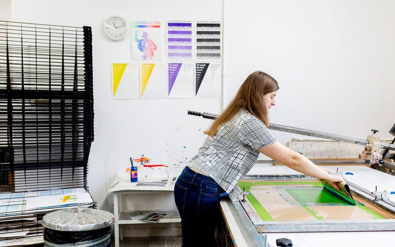 A student at Norwich University of the Arts lays out print work in the print studio at Norwich University of the Arts