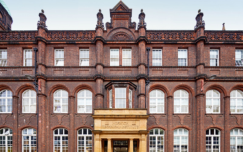 Close up photo of NUA's St Georges building, a big red brick building with lots of windows and sandstone pillars