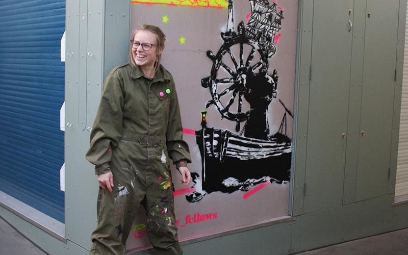 A young woman wearing glasses and khaki overalls smiling and stood next to a spray painted mural