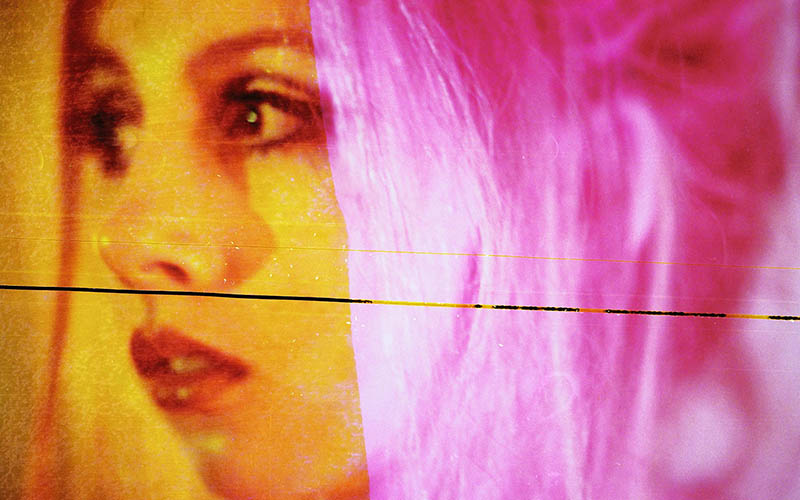 Close up photo brightly tinted with yellow and pink of a young woman's face looking left