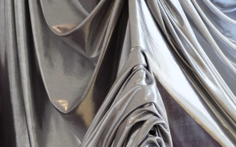 Close up of silver fabric draped over a metal object