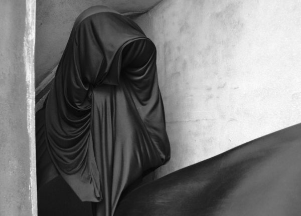 Emily Cannell, MA Fashion - Monochrome photo of a figure draped in swathes of dark fabric against a stone background