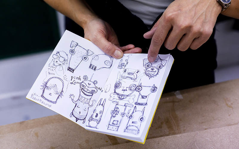 Photo of a notebook open with lots of small drawings of dogs on the pages and hands pointing to one of the drawings