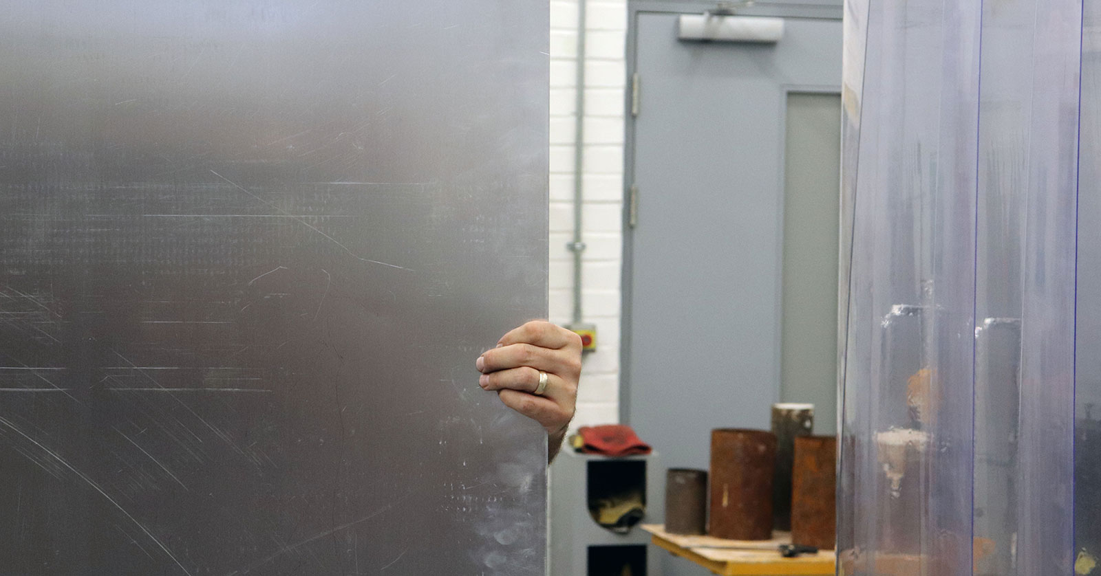 A hand holding a piece of metal in the 3D workshop at Norwich University of the Arts