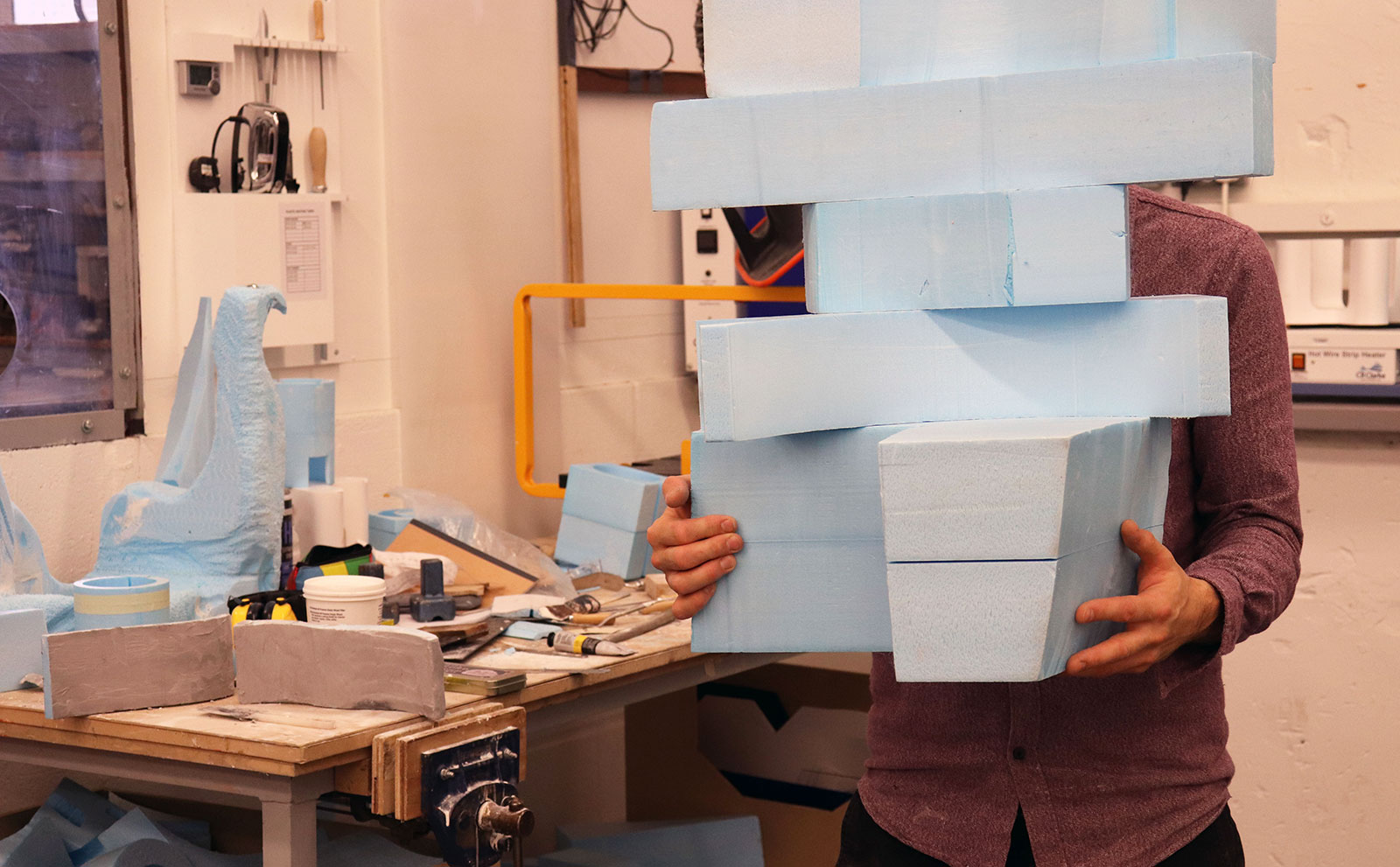 A technician in the 3D workshop holding blocks of material at Norwich University of the Arts