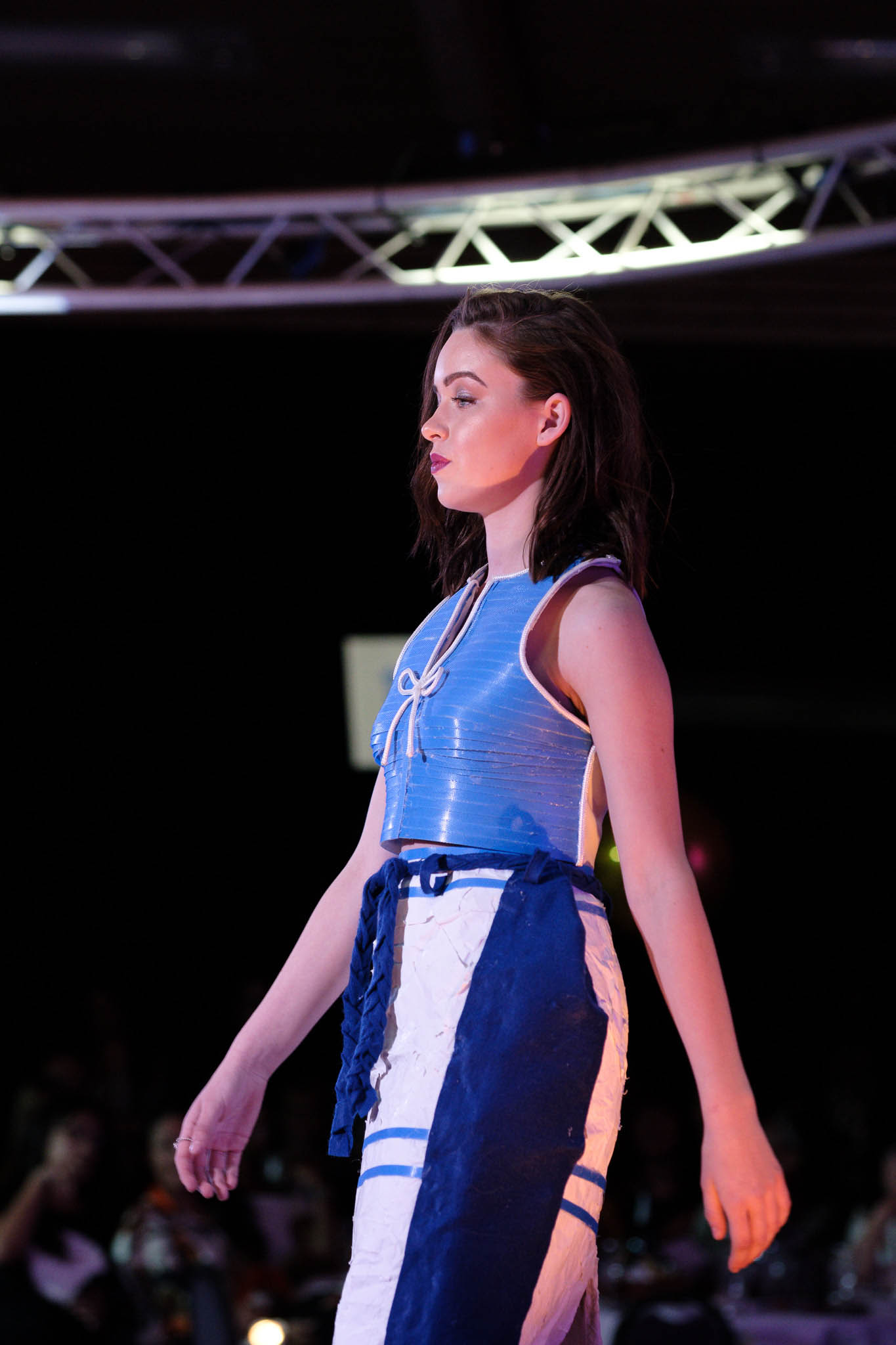 Model on catwalk at fashion show wearing blue and white dress made of recycled material